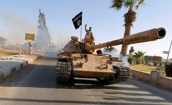 ISIS fighters on a tank take part in a military parade along the streets of northern Raqqa province, Syria June 30, 2014