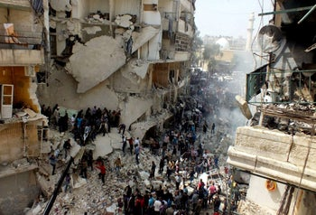 Syrian citizens searching for bodies in the rubble of damaged buildings that were attacked by Syrian regime airstrikes, in the al-Ansari neighborhood of Aleppo, Syria. April 7, 2013