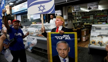 Likud party supporters, one wearing a mask depicting U.S. President Donald Trump, holding election campaign placards, one depicting Israeli Prime Minister Benjamin Netanyahu, in Jerusalem's Mahaneh Yehuda market, April 7, 2019.