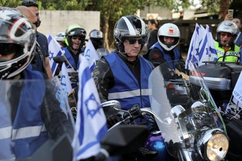 Kahol Lavan leader Benny Gantz sitting on a motorbike before leading a motorcade of motorcycles as part of an election campaign event, near the party headquarters in Tel Aviv, April 7, 2019.