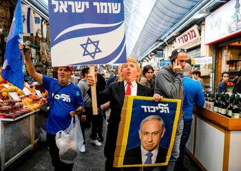 """A Netanyahu supporter wearing a Donald Trump mask with a sign reading in Hebrew """"guardian of Israel"""" and a portrait of Netanyahu. Mahane Yehuda market, Jerusalem. April 7, 2019"""