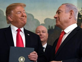 U.S. President Donald Trump smiles at Prime Minister Benjamin Netanyahu, right, after signing a proclamation on recognizing the Golan Heights, White House, Washington, March 25, 2019.