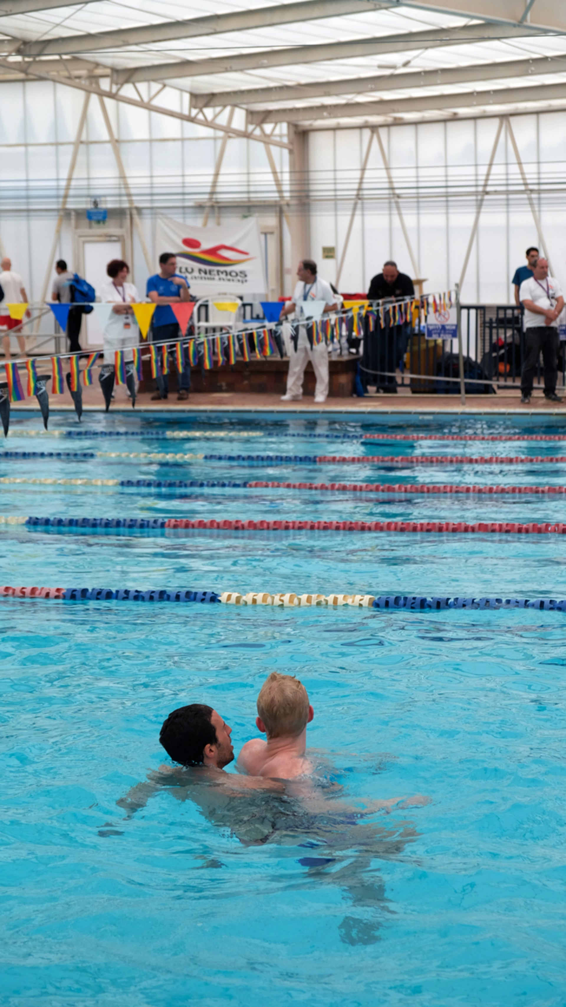 A single strand of gay pride flags strung alongside the Ramat Aviv pool was practically the only sign that something unusual was taking place there.