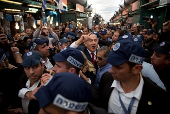 Netanyahu is escorted by security guards during a visit to the Hatikva market in Tel Aviv, Israel, on Tuesday, April 2, 2019.