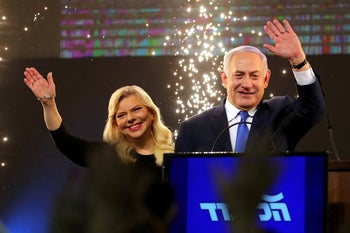 Israeli Prime Minister Benjamin Netanyahu and his wife Sara wave as Netanyahu speaks at the party headquarters in Tel Aviv, April 10, 2019.