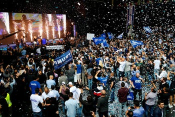 Supporters of the Israeli Likud party celebrate as Prime Minister Benjamin Netanyahu waves to them at its headquarters in Tel Aviv, April 9, 2019.