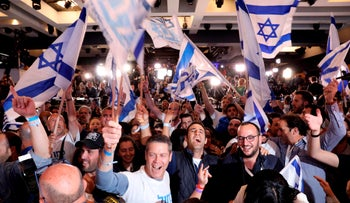 Supporters of the Blue and White (Kahol Lavan) political alliance celebrate after watching a tv poll at the alliance headquarters in Tel Aviv on April 9, 2019.