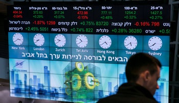 A man stands in front of an electronic board displaying market data at the Tel Aviv Stock Exchange in Israel, January 29, 2017.