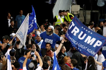 A supporter of Israeli Prime Minister Benjamin Netanyahu's Likud party waves a Donald Trump 'Make America Great Again' flag on election night at the party headquarters in Tel Aviv, Israel. April 10, 2019
