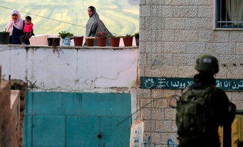 Palestinian women look at an Israeli soldier as he stands guard in a street in the northern West Bank village of Salem, east of Nablus. March 18, 2019
