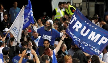 A supporter of Israeli Prime Minister Benjamin Netanyahu's Likud party waves flags, one bearing the name of U.S. President Donald Trump, as the crowd reacts to exit polls in Israel's parliamentary election at the party headquarters in Tel Aviv, Israel April 10, 2019