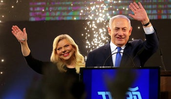 Prime Minister Benjamin Netanyahu and his wife Sara wave as Netanyahu speaks following the announcement of exit polls in Israel's parliamentary election at the party headquarters in Tel Aviv, Israel April 10, 2019.