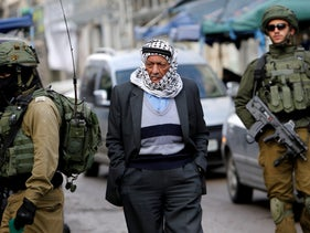 FILE PHOTO: A Palestinian man passes Israeli soldiers in the West Bank city of Hebron January 23, 2018.