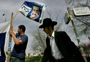An Ultra-Orthodox Jew walks by a supporter of the Labor party waving a flag with a picture of the party's then-leader Amir Peretz, in Jerusalem., March 24, 2006