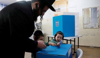 An ultra-Orthodox father helps his kids cast his ballot at a polling station in Jerusalem. April 9, 2019