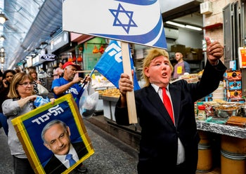 A supporter of Israeli Prime Minister Benjamin Netanyahu wearing a Donald Trump mask marches along an alley of the Machane Yehuda market in Jerusalem on April 7, 2019