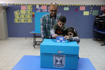 An Israeli-Arab father casts a ballot together with his children, as Israelis vote in a parliamentary election, at a polling station in Umm al-Fahm, Israel April 9, 2019