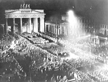 Nazi troops bearing torches march in Berlin to celebrate Hitler taking over power on Jan. 30, 1933