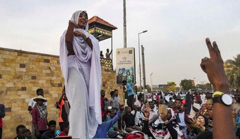 Alaa Salah, a Sudanese woman propelled to internet fame earlier this week after clips went viral of her leading powerful protest chants against President Omar al-Bashir, addresses protesters during a demonstration in front of the military headquarters in the capital Khartoum on April 10, 2019