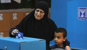 An Arab Israeli woman casts her vote during Israel's parliamentary elections on April 9, 2019 at a polling station in the northern Israeli town of Taiyiba