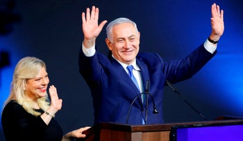 Israeli Prime Minister Benjamin Netanyahu greets supporters with his wife Sara at his Likud Party headquarters in Tel Aviv on election night early on April 10, 2019