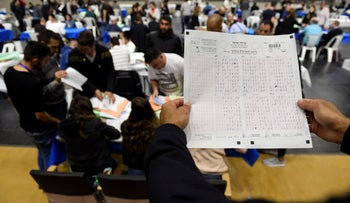 Election official holds a form as votes in Israel's general election are counted in Haifa, April 10, 2019.