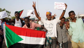 udanese demonstrators hold a national flag and chant slogans as they protest against the army's announcement that President Omar al-Bashir would be replaced by a military-led transitional council, outside Defence Ministry in Khartoum, Sudan April 11, 2019.