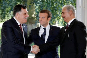FILE PHOTO: French President Emmanuel Macron stands between Libyan Prime Minister Fayez al-Serraj (L), and General Khalifa Haftar (R), commander in the Libyan National Army (LNA), who shake hands after talks over a political deal to help end Libya's crisis in La Celle-Saint-Cloud near Paris, France, July 25, 2017.