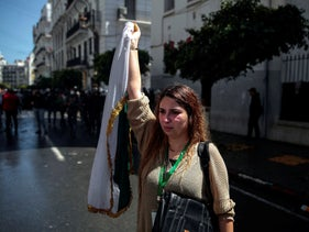A woman waves an Algerian flag after police attempted to disperse a demonstration for students in Algiers, Algeria, Tuesday, April 9, 2019.