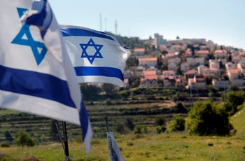 A photo taken on April 12, 2019 shows Israeli flags in front of a partial view of the Israeli settlement of Efrat situated on the southern outskirts of the West Bank city of Bethlehem.