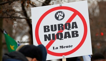 File photo: A sign opposing religious attire is displayed during protests by groups La Meute and Storm Alliance in Quebec, Canada November 2017.