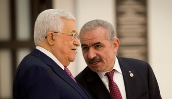 Palestinian Prime Minister Mohammad Shtayeh talks with Palestinian President Mahmoud Abbas during a swearing in of the new government in Ramallah, April 13, 2019.