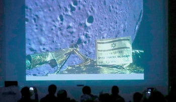 People watch a screen showing a picture taken by the Beresheet spacecraft of the moon surface as the craft approaches and before it crashed during the landing, in Netanya, April 11, 2019.