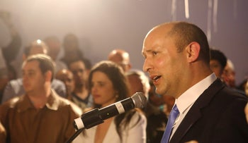 Naftali Bennett speaks as Ayelet Shaked is seen in the background after voting ends in Israel's general election, at Hayamin Hehadash headquarters in Bnei Brak, April 9, 2019.