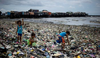 Children collect plastic water bottles among the garbage washed ashore as a result of a storm surge of typhoon Haima at the Manila Bay on October 20, 2016.