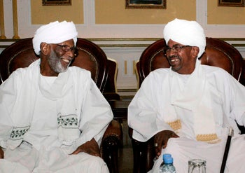 Sudan's ex-President Omar al-Bashir (R) and breakaway Islamist Hassan al-Turabi at a meeting at the presidential guest house in the capital Khartoum. March 14, 2014