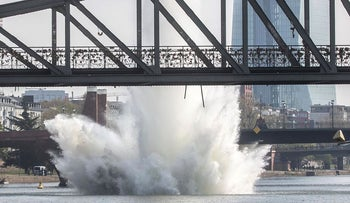 A large water fountain rises behind the Iron Bridge when a 250 kilogram US-American bomb from the Second World War in the Main River is detonated with a blast in Frankfurt, Germany, Sunday, April 14, 2019