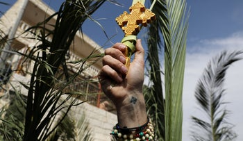 A Christian worshipper holds a wooden cross attached to a palm frond during a Palm Sunday procession on the Mount of Olives in Jerusalem, April 14, 2019.