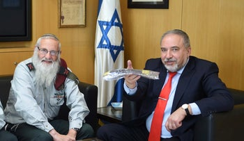 Yisrael Beiteinu's Avigdor Lieberman gives the Chief Rabbi of the IDF permission to sell leavened goods to non-Jews before Passover in a traditional ceremony at IDF headquarters, March 26, 2018.
