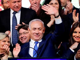 Israeli Prime Minister Benjamin Netanyahu (C) waves to supporters at his Likud Party headquarters in the Israeli coastal city of Tel Aviv on election night early on April 10, 2019.