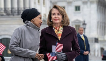 Rep. Ilhan Omar whispers to Speaker of the House Nancy Pelosi as Democrats rally outside the Capitol in Washington, March 8, 2019.