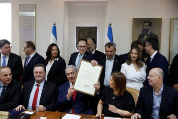 Israeli PM Benjamin Netanyahu holds a proclamation signed by U.S. President Donald Trump recognizing Israel's sovereignty over the Golan Heights during the weekly cabinet meeting in Jerusalem. April 14, 2019