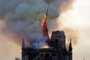 The steeple of the landmark Notre-Dame Cathedral collapses as the cathedral is engulfed in flames in central Paris on April 15, 2019