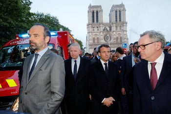 French President Emmanuel Macron watches as the iconic cathedral goes up in flames, Paris, France, April 15, 2019.