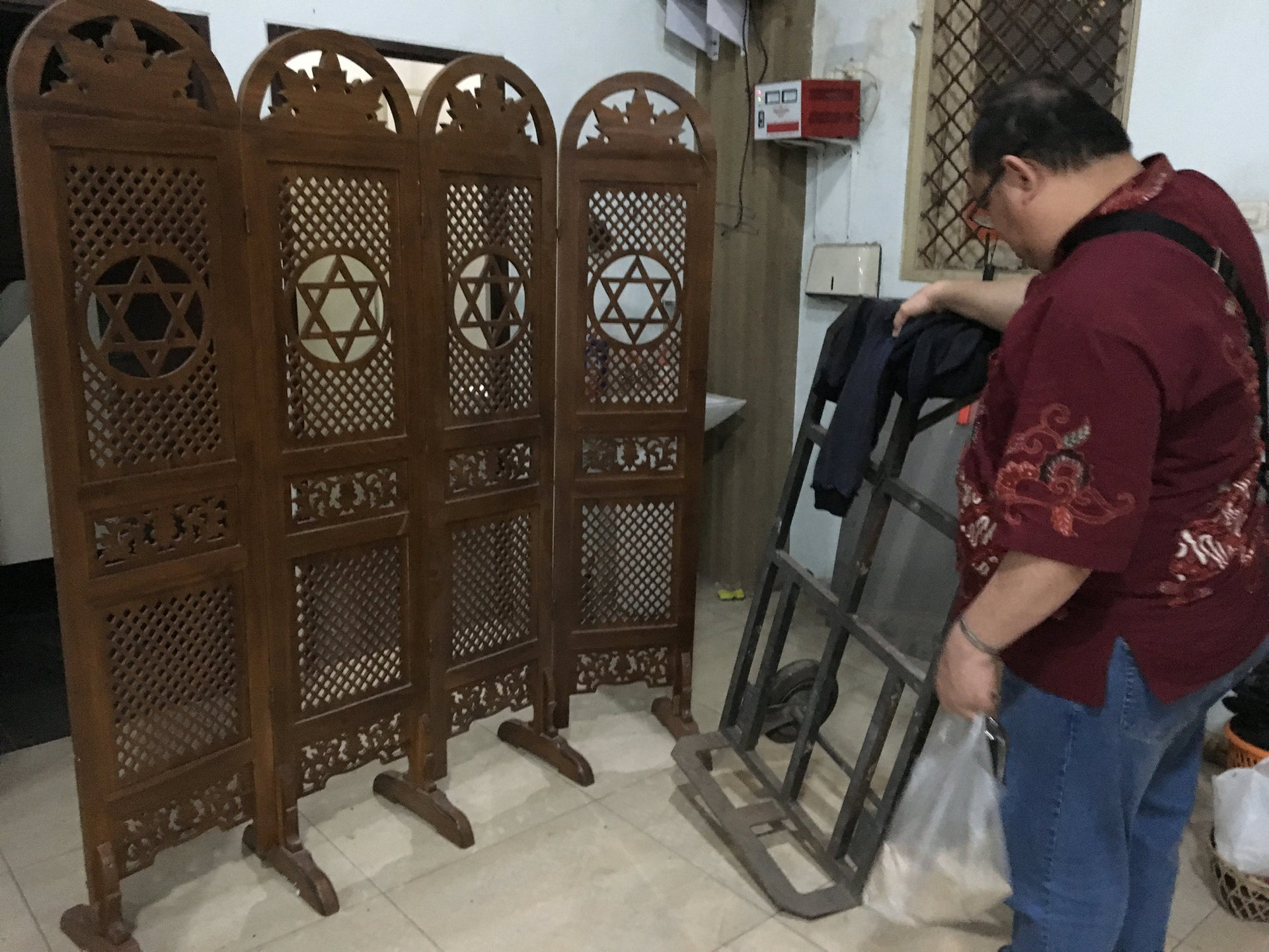 After Shabbat prayers are over, Rudi C. rearranges a wooden divider with an engraving of the Magen David, to block the view of the stairs leading to the shul in Jakarta.
