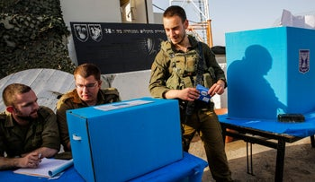 An Israeli soldier prepares to cast his vote at the Erez army base in the south of Israel near the border with the Gaza strip on April 7, 2019