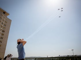 File photo: A man watches a flyover on Independence Day on a Tel Aviv beach.