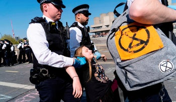 Police officers arrest and carry away a climate change activist from a demonstration blocking Waterloo Bridge in London, United Kingdom, April 20, 2019.