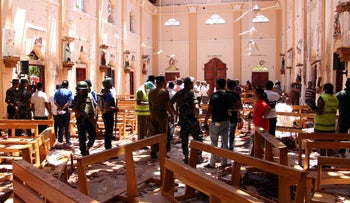 Sri Lankan security personnel walk next to dead bodies on the floor amid blast debris at St. Anthony's Shrine following an explosion in the church in Kochchikade in Colombo on April 21, 2019.