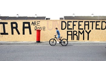 "A pedestrian walks past graffiti that has been amended to read ""IRA are done. Defeated Army"" instead of ""IRA undefeated Army"" in the Creggan area of Derry (Londonderry) in Northern Ireland on April 20, 2019 close by the scene where a journalist was fatally shot amid rioting on April 18"